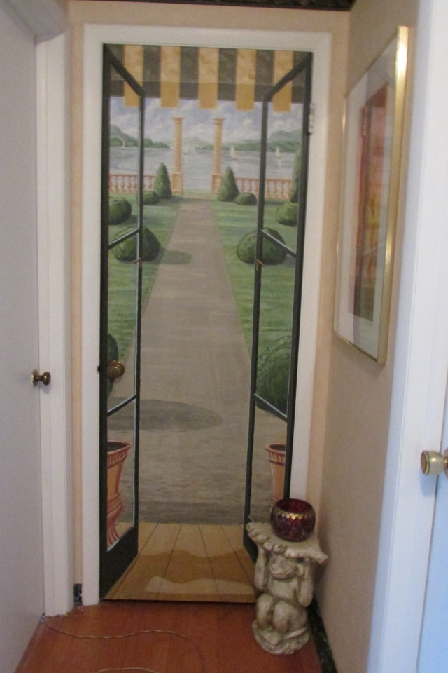 A door at the end of a long narrow hallway.