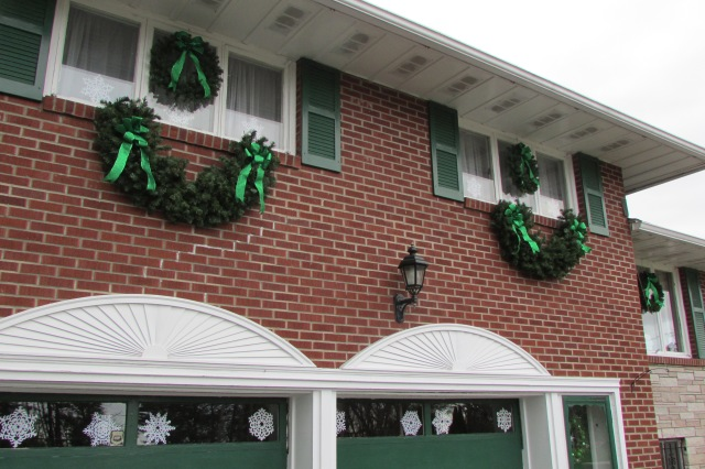 and large artificial evergreen swags and cut paper snowflakes add visual interest to the front facade of my house.