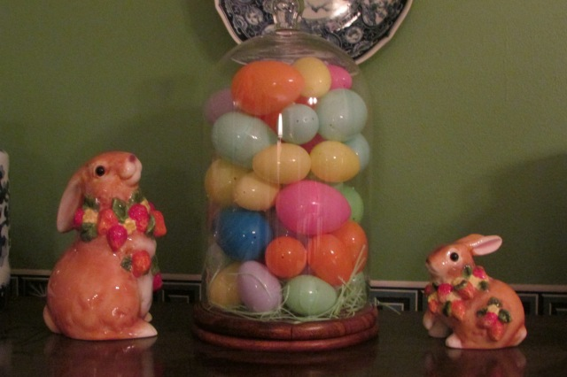 Arranging Easter Eggs and other things under a glass dome.