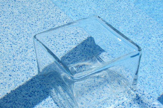 A clear glass vase, on the first step in the pool, used to determine if it evaporation or some other kind of leak in the in-ground pool.
