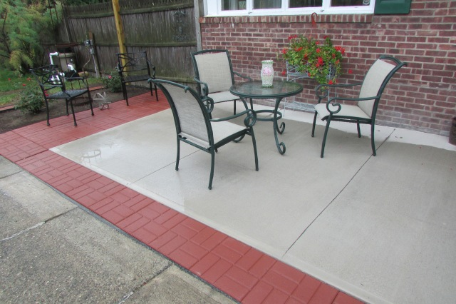 Extending a poured cement patio with sixteen inch square brick-face stepping stone/ patio pavers.